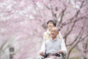 車椅子で散歩するシニア夫婦の写真素材 [FYI04558380]