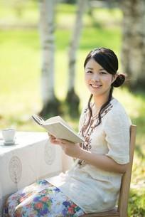 自然の中で読書をする女性の写真素材 [FYI04558407]