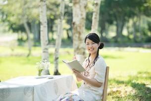自然の中で読書をする女性の写真素材 [FYI04558412]