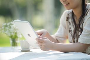 自然の中でタブレットを操作する女性の手元の写真素材 [FYI04558418]
