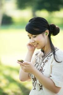自然の中で音楽を聴く女性の写真素材 [FYI04558427]