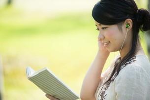 自然の中で読書をする女性の写真素材 [FYI04558429]