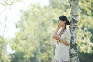 自然の中で音楽を聴く女性の写真素材 [FYI04558430]