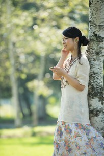 自然の中で音楽を聴く女性の写真素材 [FYI04558431]