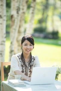 自然の中でパソコンを操作する女性の写真素材 [FYI04558434]