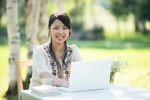 自然の中でパソコンを操作する女性の写真素材 [FYI04558435]