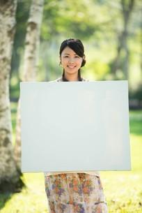 自然の中でホワイトボードを持つ女性の写真素材 [FYI04558443]