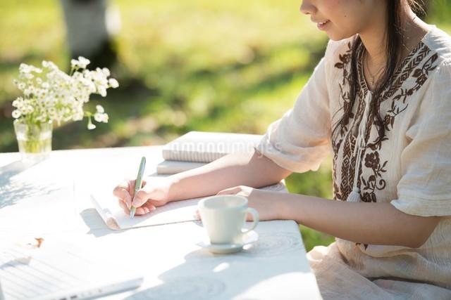 自然の中で手紙を書く女性の写真素材 [FYI04558448]