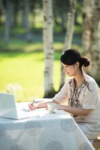 自然の中で手紙を書く女性の写真素材 [FYI04558450]