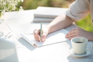 手紙を書く女性の手元の写真素材 [FYI04558453]