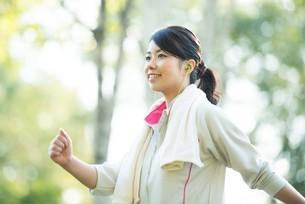 自然の中でウォーキングをする女性の横顔の写真素材 [FYI04558457]