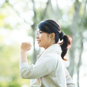 自然の中でジョギングをする女性の横顔の写真素材 [FYI04558460]