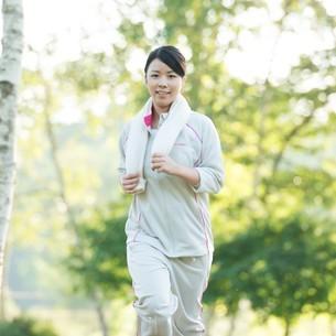 自然の中でジョギングをする女性の写真素材 [FYI04558462]