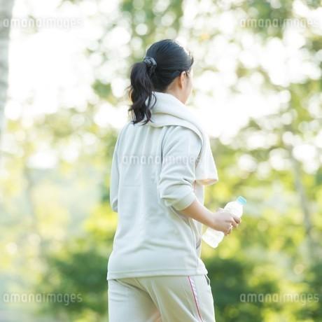 自然の中で水分補給をする女性の後ろ姿の写真素材 [FYI04558464]
