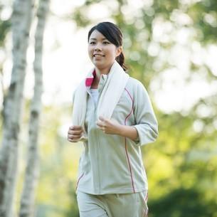 自然の中でジョギングをする女性の写真素材 [FYI04558465]