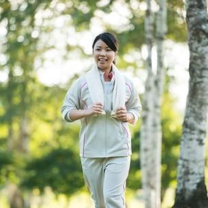 自然の中でジョギングをする女性の写真素材 [FYI04558468]