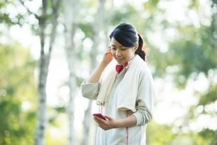 自然の中で音楽を聴くスポーティーな女性の写真素材 [FYI04558469]