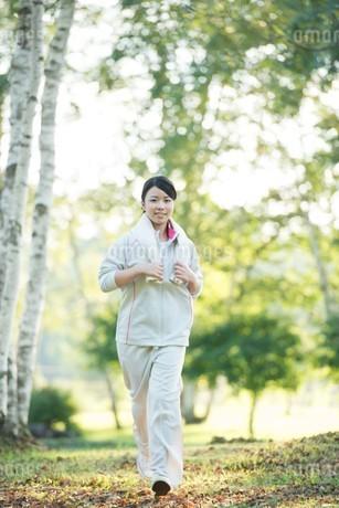 自然の中でジョギングをする女性の写真素材 [FYI04558470]
