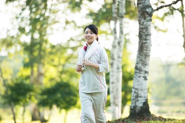 自然の中でジョギングをする女性の写真素材 [FYI04558473]
