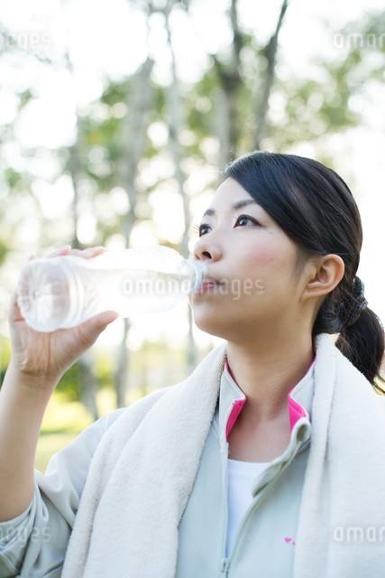 自然の中で水分補給をする女性の写真素材 [FYI04558474]