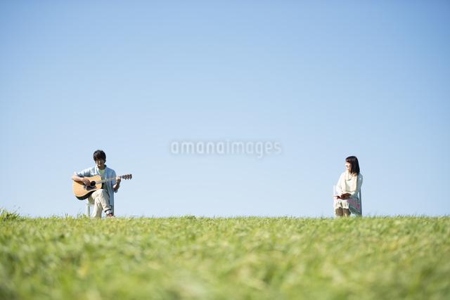 草原でギターを弾く男性と本を読む女性の写真素材 [FYI04558479]