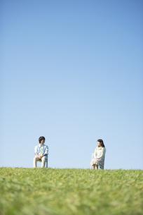 草原で椅子に座り談笑するカップルの写真素材 [FYI04558480]