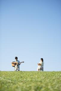 草原でギターを弾く男性と本を読む女性の写真素材 [FYI04558484]