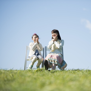 草原で椅子に座る親子の写真素材 [FYI04558511]
