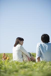 草原でピクニックをするカップルの後ろ姿の写真素材 [FYI04558534]