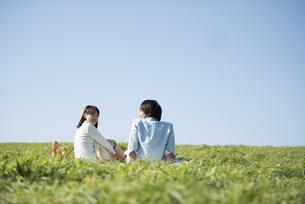 草原でピクニックをするカップルの写真素材 [FYI04558538]