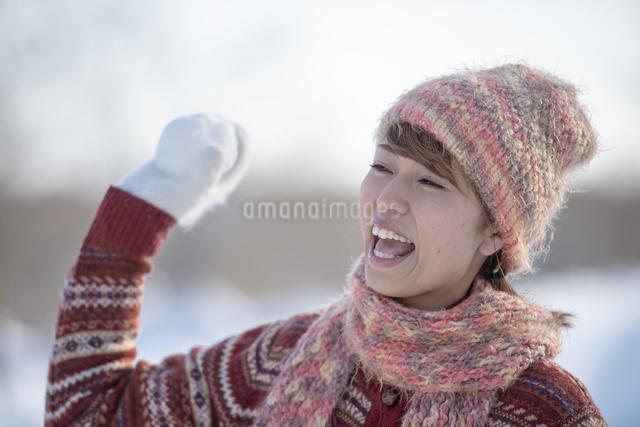 雪玉を持ち微笑む女性の写真素材 [FYI04558623]