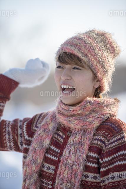 雪玉を持ち微笑む女性の写真素材 [FYI04558625]