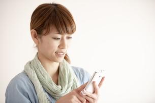 スマートフォンを操作する女性の写真素材 [FYI04558635]