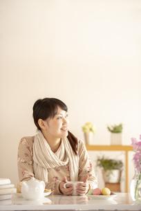 コーヒーカップを持ち微笑む女性の写真素材 [FYI04558747]