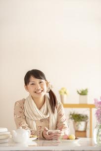 コーヒーカップを持ち微笑む女性の写真素材 [FYI04558748]