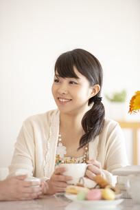 コーヒーカップを持ち微笑む女性の写真素材 [FYI04558761]