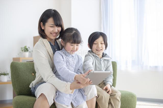 タブレットを操作する親子の写真素材 [FYI04558804]