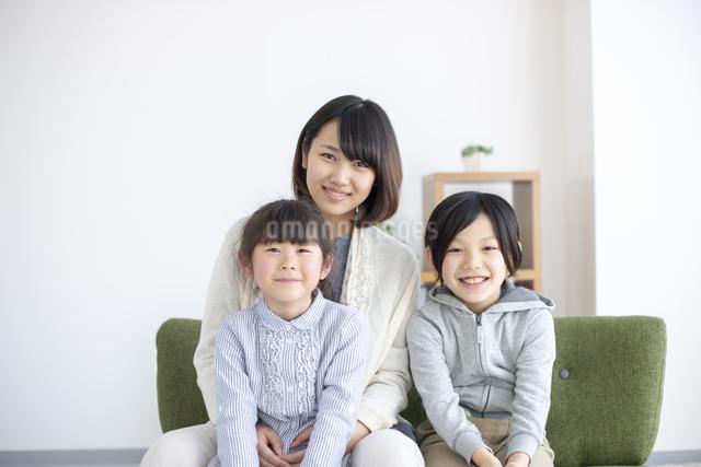 ソファーでくつろぐ笑顔の親子の写真素材 [FYI04558805]