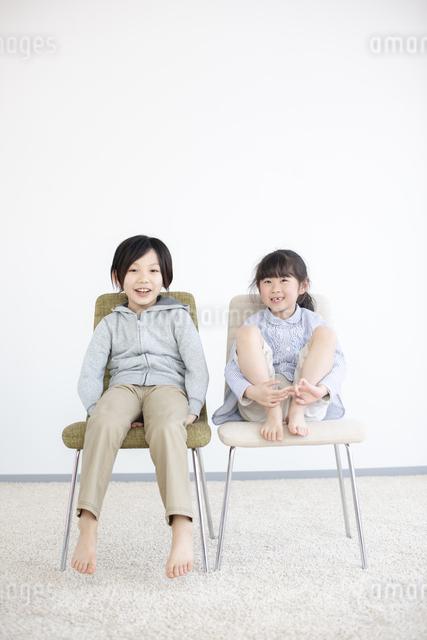 椅子に座る笑顔の子供の写真素材 [FYI04558807]