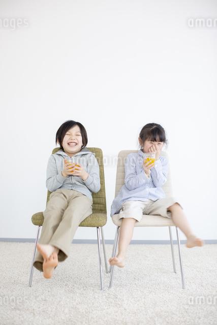 椅子に座りジュースを飲む子供の写真素材 [FYI04558808]