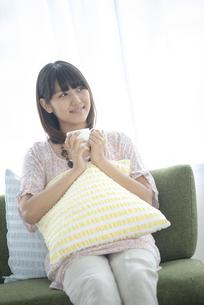 ソファーに座りコーヒーカップを持つ女性の写真素材 [FYI04558816]
