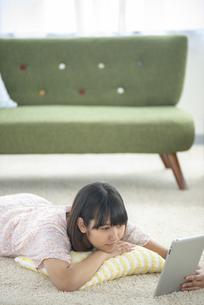 床に寝転びタブレットPCを見る女性の写真素材 [FYI04558819]