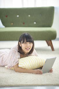 床に寝転びタブレットPCを持つ女性の写真素材 [FYI04558821]