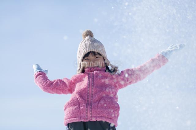 雪で遊ぶ笑顔の女の子の写真素材 [FYI04558830]