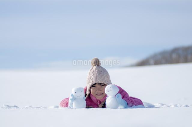 雪原で雪だるまと微笑む女の子の写真素材 [FYI04558831]