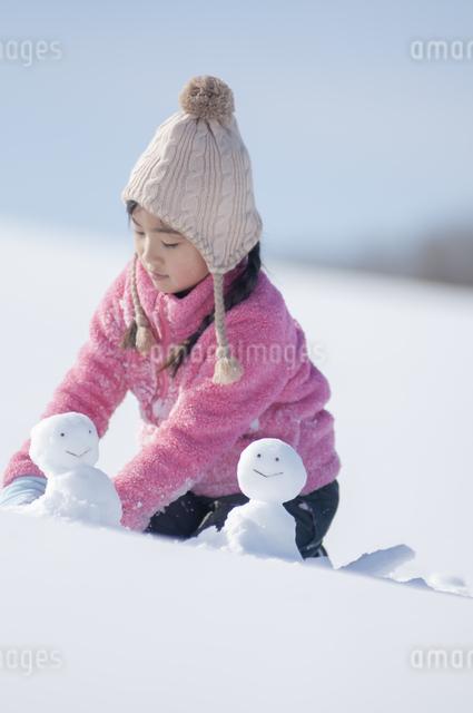 雪原で雪だるまを作る女の子の写真素材 [FYI04558836]