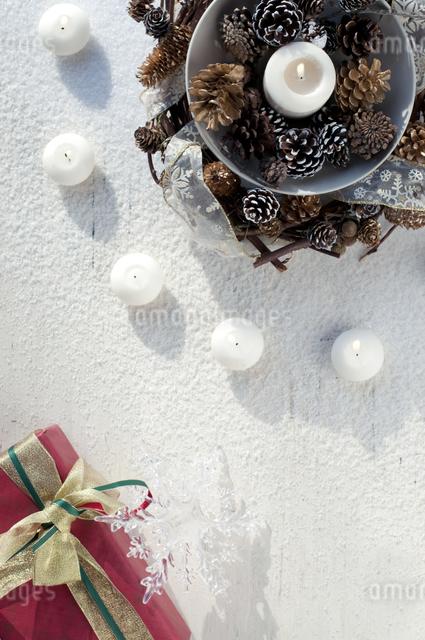 キャンドルと松ぼっくりとプレゼントの写真素材 [FYI04559489]