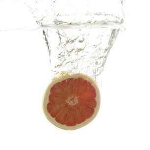 水に落としたピンクグレープフルーツの写真素材 [FYI04559641]