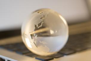 ガラスの地球とノートパソコンの写真素材 [FYI04560204]