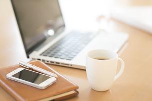 机の上のコーヒーとビジネスグッズの写真素材 [FYI04560206]